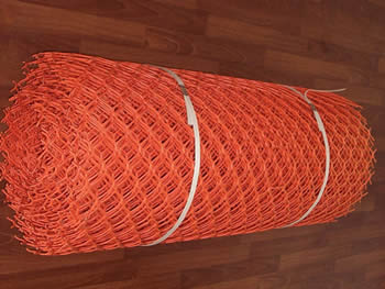 A roll of orange diamond mesh type safety barrier fence.