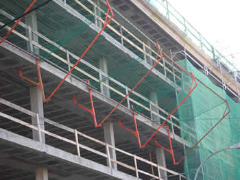 The green horizontal debris netting is installed around the building.