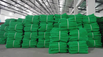 The green construction safety netting is packed in bundles.